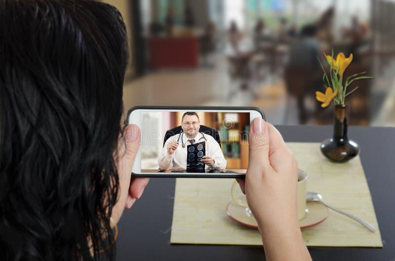 La femme contacte le docteur d'e-santé par le téléphone portable photos stock