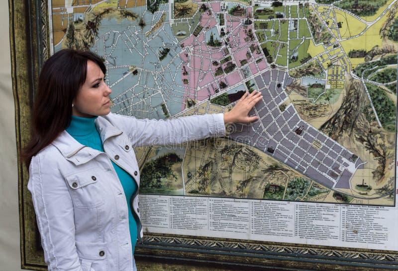 La femme contemple la carte de ville sur le mur images stock