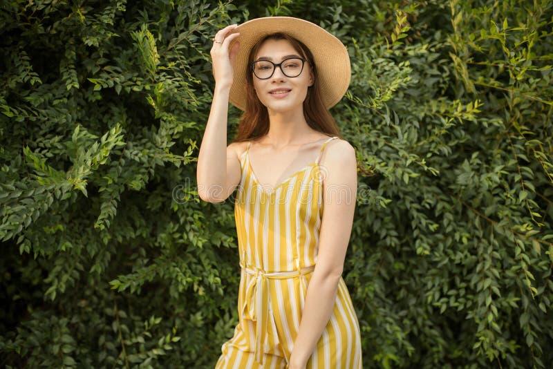 La femme contentée dans une salopette et un chapeau jaunes se tient dans la ville sur la rue photos libres de droits