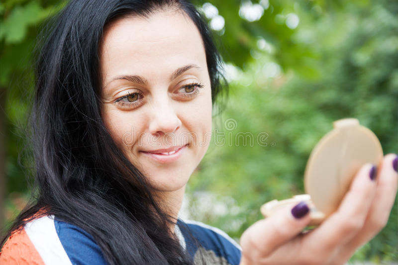 La femme corrige le maquillage photo stock