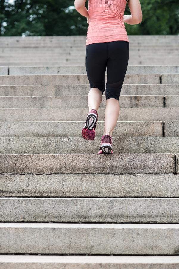 La femme courant sur des étapes dans le Central Park de New York portant le sport vêtx à l'heure d'été images stock