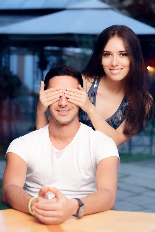 La femme couvrant Man's observe le prenant par surprise un rendez-vous avec une personne inconnue photographie stock libre de droits