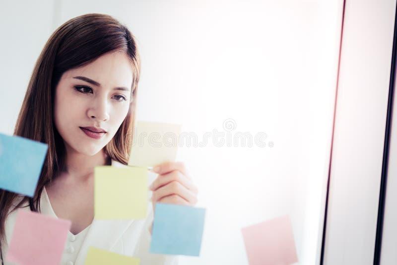 La femme créative d'affaires écrit l'idéal et le but dessus aux fenêtres image stock