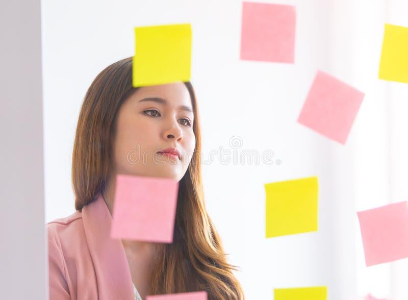 La femme créative d'affaires écrit l'idéal et le but dessus aux fenêtres photos libres de droits