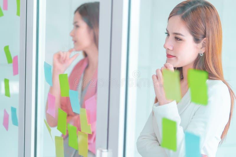 La femme créative d'affaires écrit l'idéal et le but dessus aux fenêtres photo libre de droits