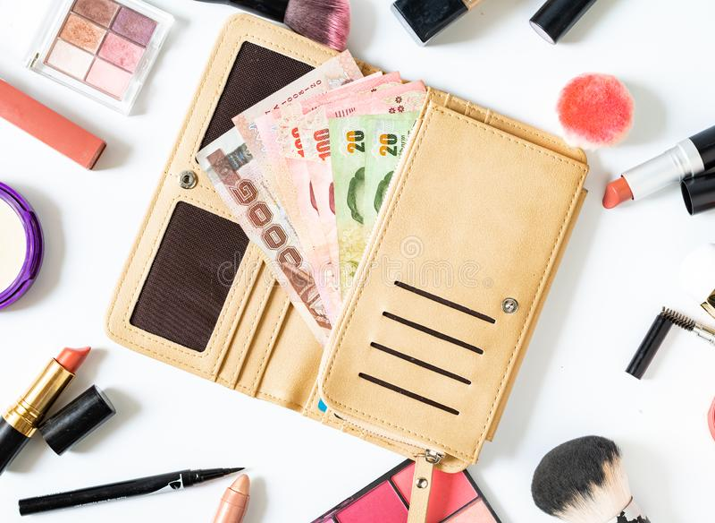 La femme dépensent l'argent pour des cosmétiques et des produits de beauté et configuration plate Concept d'achats photos stock