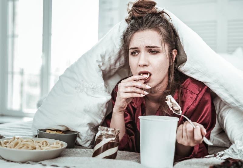 La femme déprimée mange avec excès en raison de l'effort photos stock
