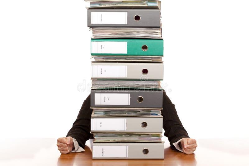 La femme désespérée d'affaires s'assied derrière la pile de dépliant photographie stock