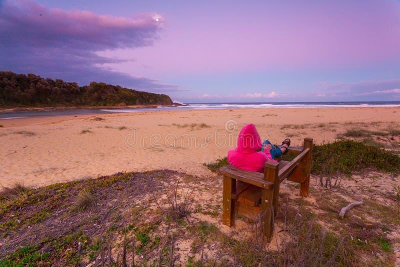 La femme détend sur la plage de négligence de banc dans le crépuscule d'après-midi images stock