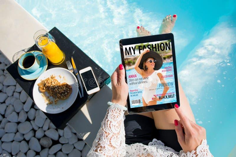 La femme détendant par la piscine et lisant l'emagazine sur le comprimé au petit déjeuner tout le contenu se composent photographie stock