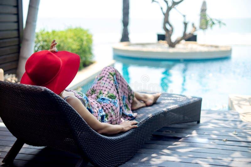 la femme détendent sur le lit pliant près de la piscine photographie stock