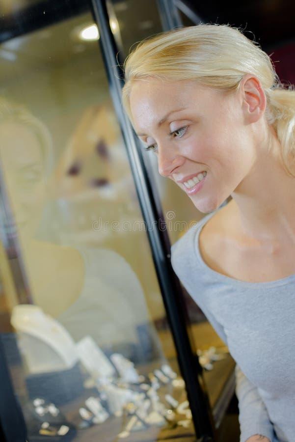 La femme d'achats choisit des bijoux dans le magasin photographie stock libre de droits