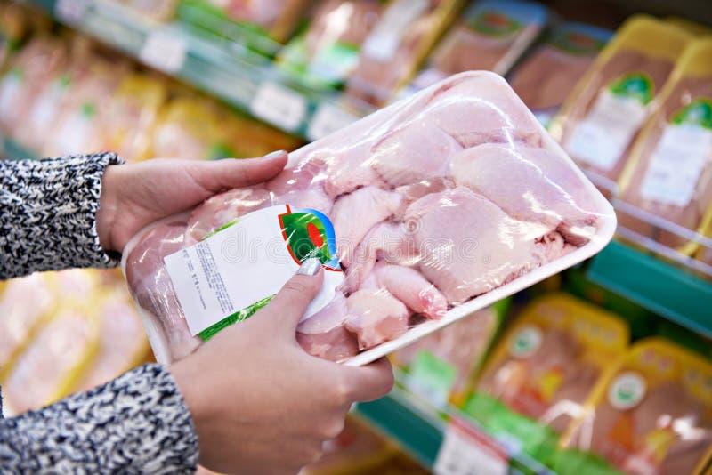 La femme d'acheteur choisit la viande de poulet dans la boutique photo libre de droits
