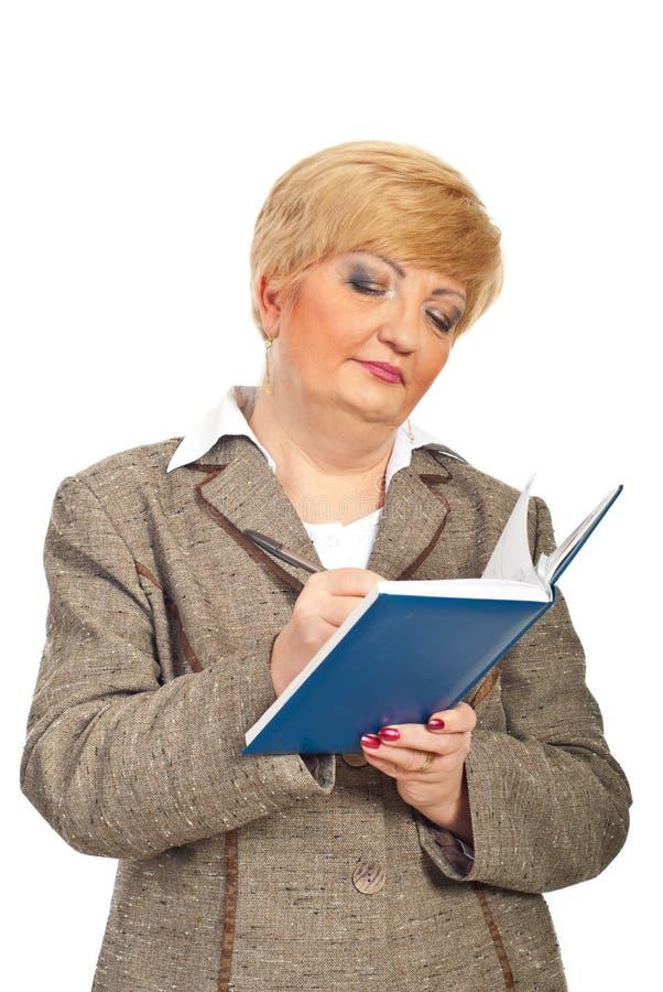La femme d'affaires âgée moyenne écrivent dans l'ordre du jour images stock