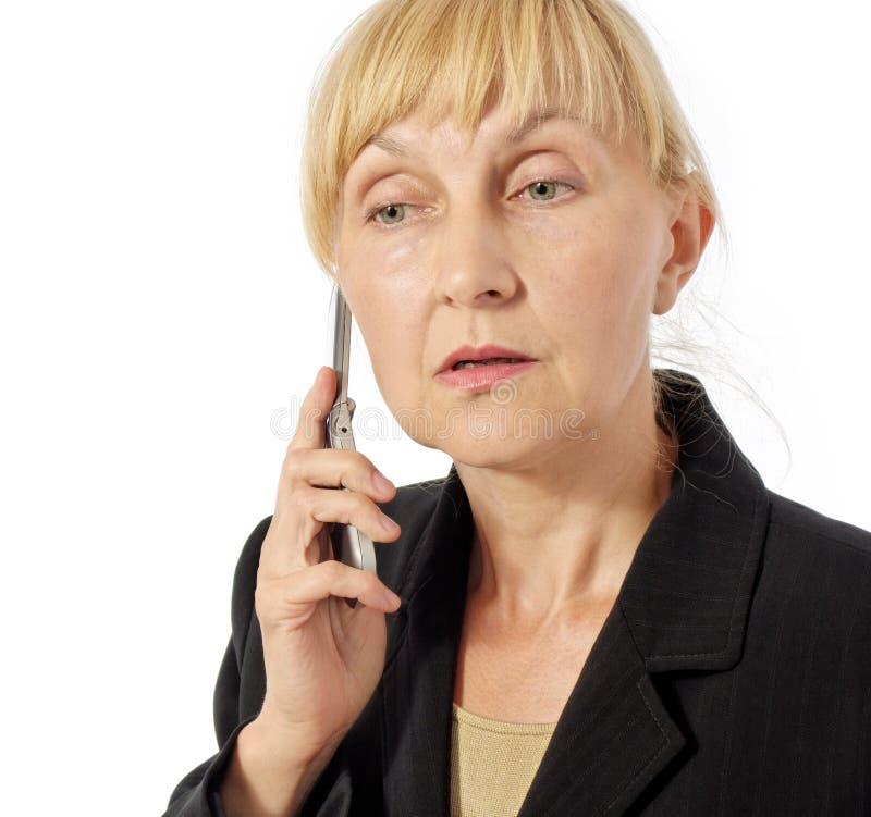 La femme d'affaires écoute le smb sur le téléphone portable image libre de droits