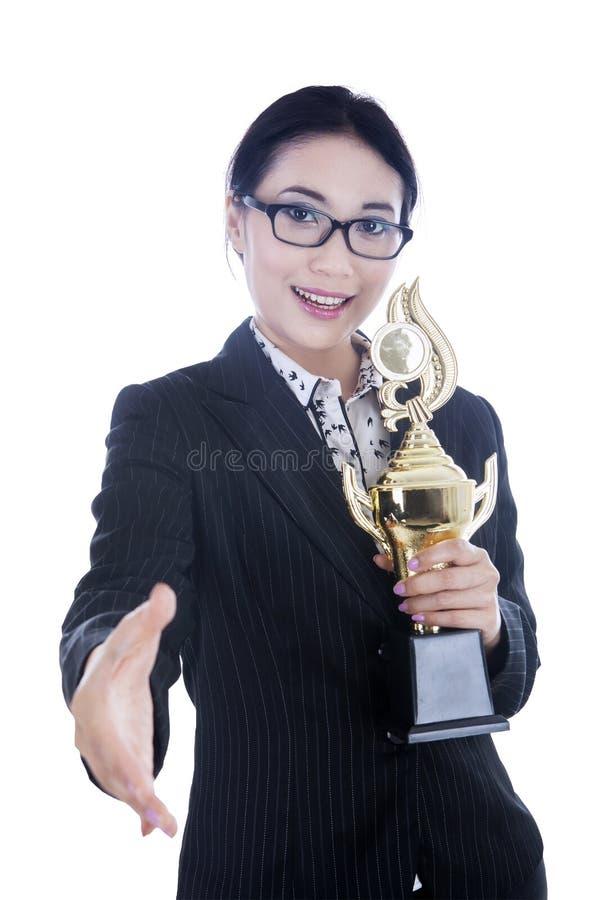 La femme d'affaires apportent le trophée et donnent la poignée de main photo stock