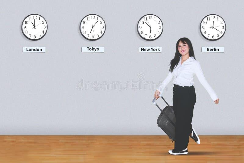 La femme d'affaires asiatique porte un bagage dans l'aéroport photographie stock