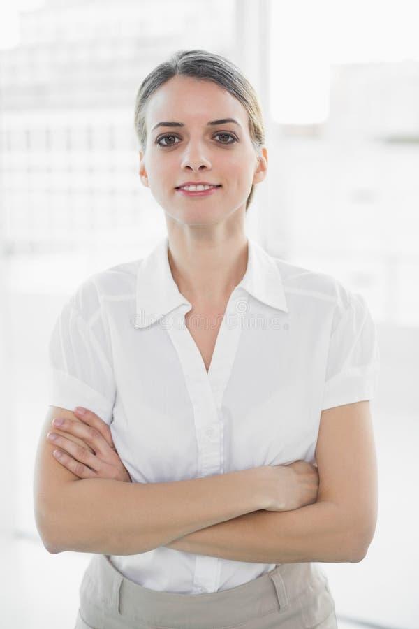 La femme d'affaires attirante posant avec des bras a croisé regarder l'appareil-photo photo stock