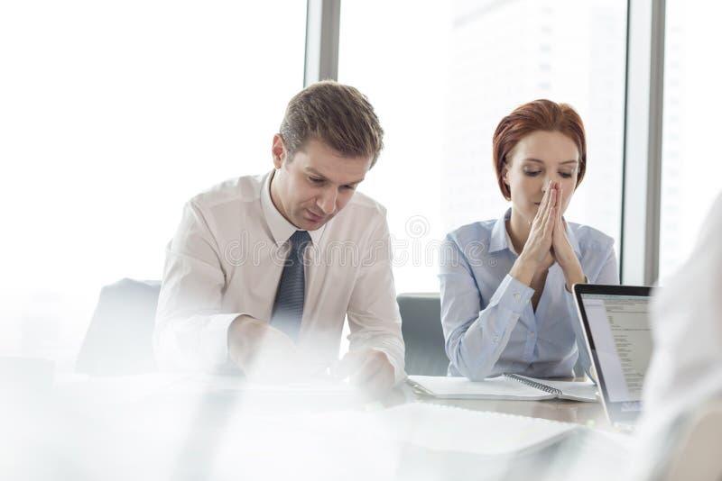 La femme d'affaires avec des mains a étreint se reposer par l'homme d'affaires dans la salle de réunion pendant se réunir au bure images stock