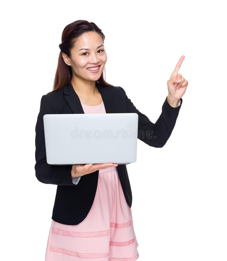 La femme d'affaires avec l'ordinateur portable et le doigt précisent images stock