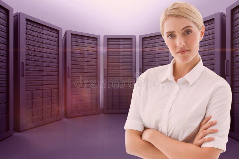 La femme d'affaires avec le bras a croisé contre la salle de serveur photo stock