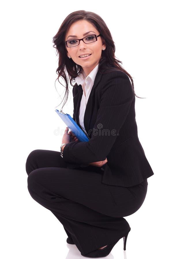 La femme d'affaires avec le presse-papiers se tapit image stock