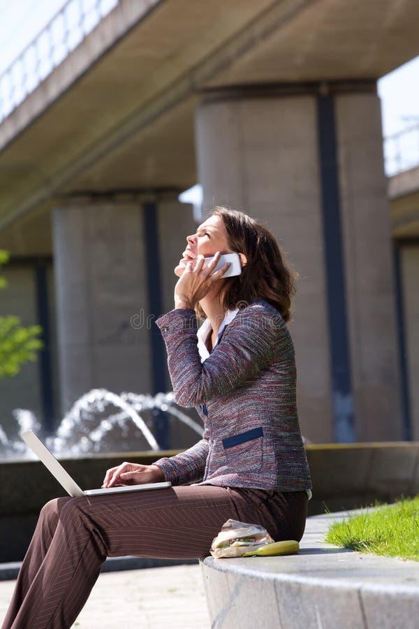La femme d'affaires avec le téléphone portable et l'ordinateur portable dans la ville se garent photographie stock