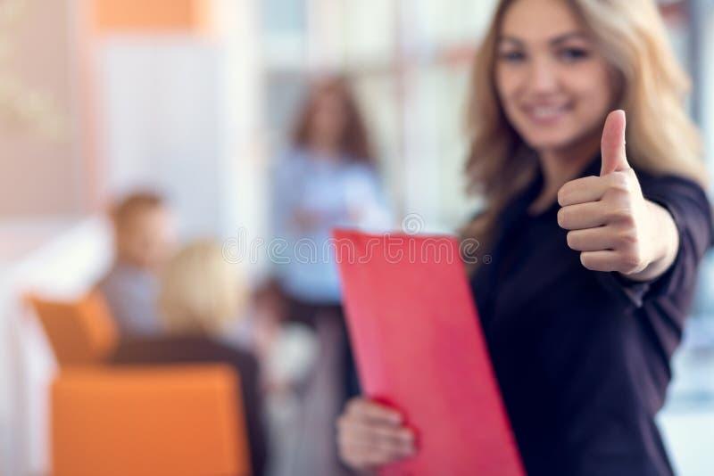 La femme d'affaires avec la position et l'équipe de dossiers joint le travail dans le lieu de réunion au bureau images stock