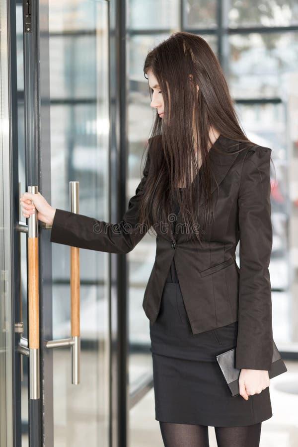 La femme d'affaires avec un bloc-notes entre dans la porte photographie stock libre de droits