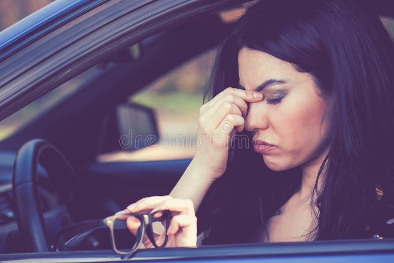La femme d'affaires ayant le mal de tête enlevant ses verres doit faire un arrêt après avoir conduit la voiture l'heure de pointe images libres de droits