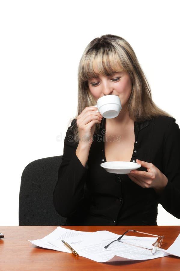 La femme d'affaires boit du café sur le lieu de travail photos stock