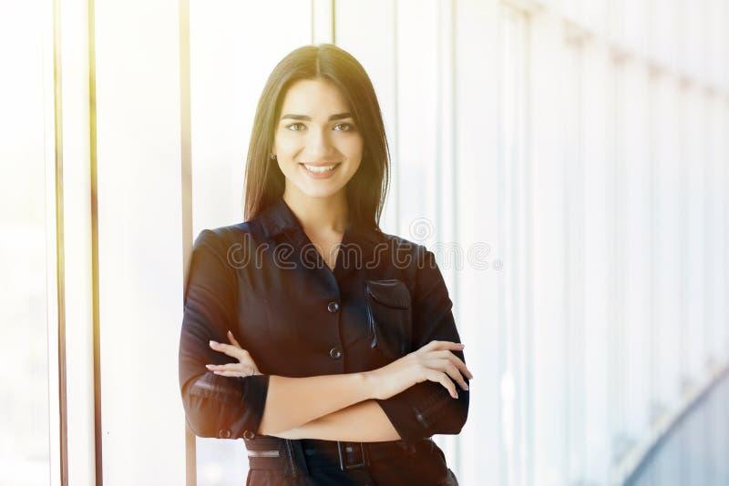 La femme d'affaires a croisé le portrait de mains dans le bureau avec les fenêtres panormic photos stock