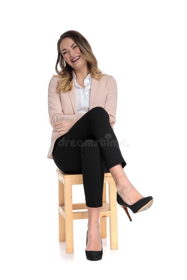 La femme d'affaires détendue s'assied sur la chaise en tailleur et le rire images libres de droits