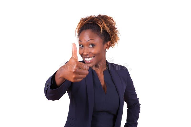 La femme d'affaires d'afro-américain faisant des pouces lèvent le geste - noir photo stock