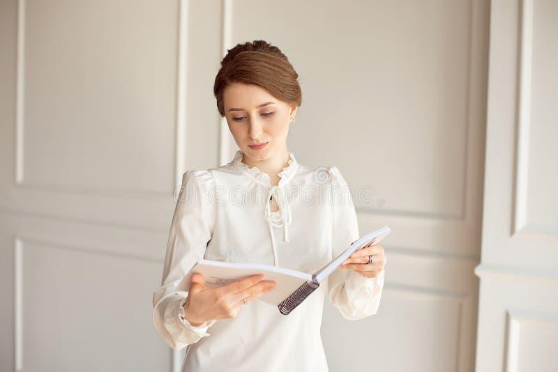 La femme d'affaires dans une chemise blanche et des pantalons noirs regarde des documents dans des mains images stock