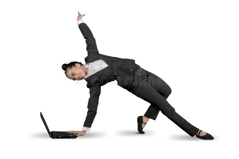 La femme d'affaires danse avec un ordinateur portable sur le studio image stock