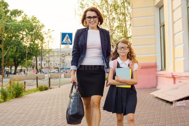La femme d'affaires de mère porte l'enfant à l'école photographie stock