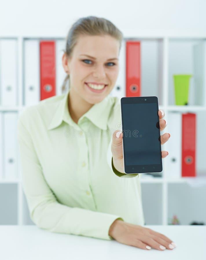 La femme d'affaires de sourire dans le bureau tiennent le téléphone portable dans des mains et montrent l'écran à l'appareil-phot photos stock