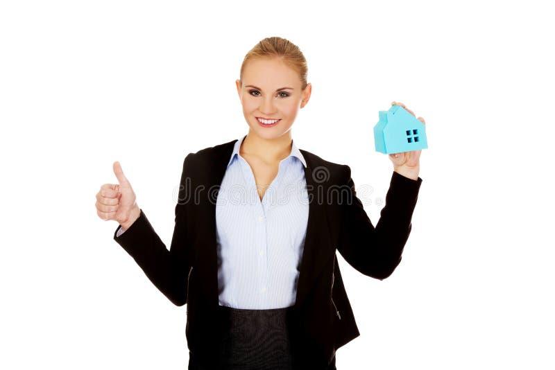 La femme d'affaires de sourire tenant une maison de papier et l'exposition manient maladroitement  photo stock