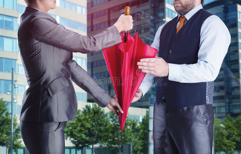 La femme d'affaires donne le parapluie à l'homme d'affaires images libres de droits