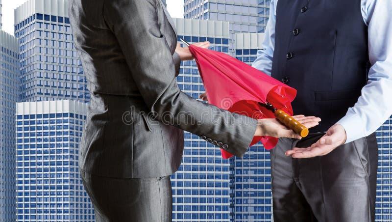 La femme d'affaires donne le parapluie à l'homme d'affaires images stock