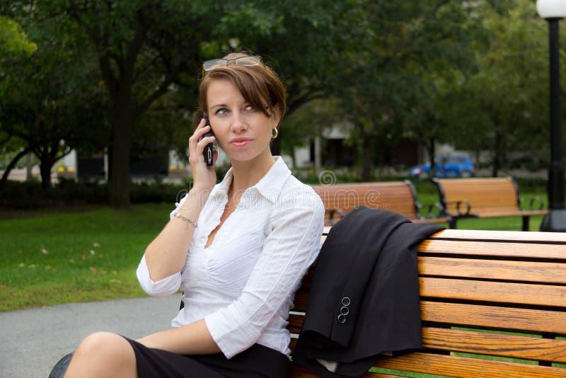 La femme d'affaires en parc parle au téléphone portable images stock