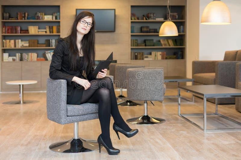 La femme d'affaires en verres s'assied sur une chaise avec le bloc-notes photo libre de droits