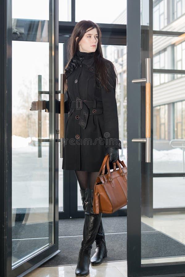 La femme d'affaires entre dans la porte en verre images stock