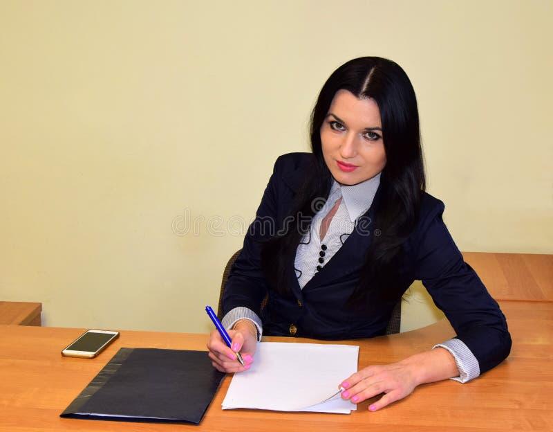 la femme d'affaires est au bureau photos stock