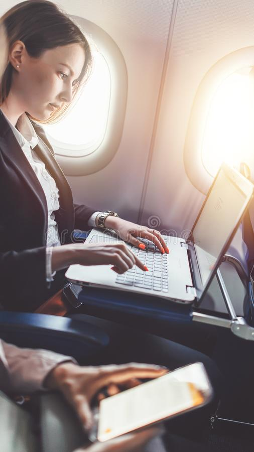 La femme d'affaires féminine travaille sur son projet utilisant un ordinateur portable tout en se reposant dans un avion photographie stock libre de droits