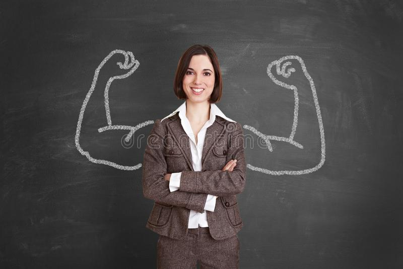 La femme d'affaires forte se tient devant le tableau noir image stock