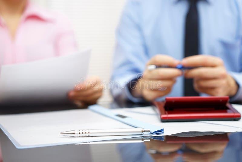 La femme d'affaires lit le contrat à l'homme d'affaires dans le backgro de tache floue image libre de droits