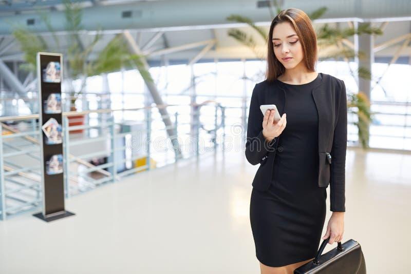 La femme d'affaires lit un message sur le smartphone photo libre de droits