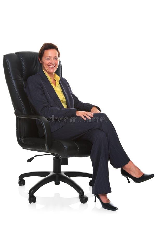 La femme d'affaires mûre s'est assise dans la présidence en cuir   photos stock